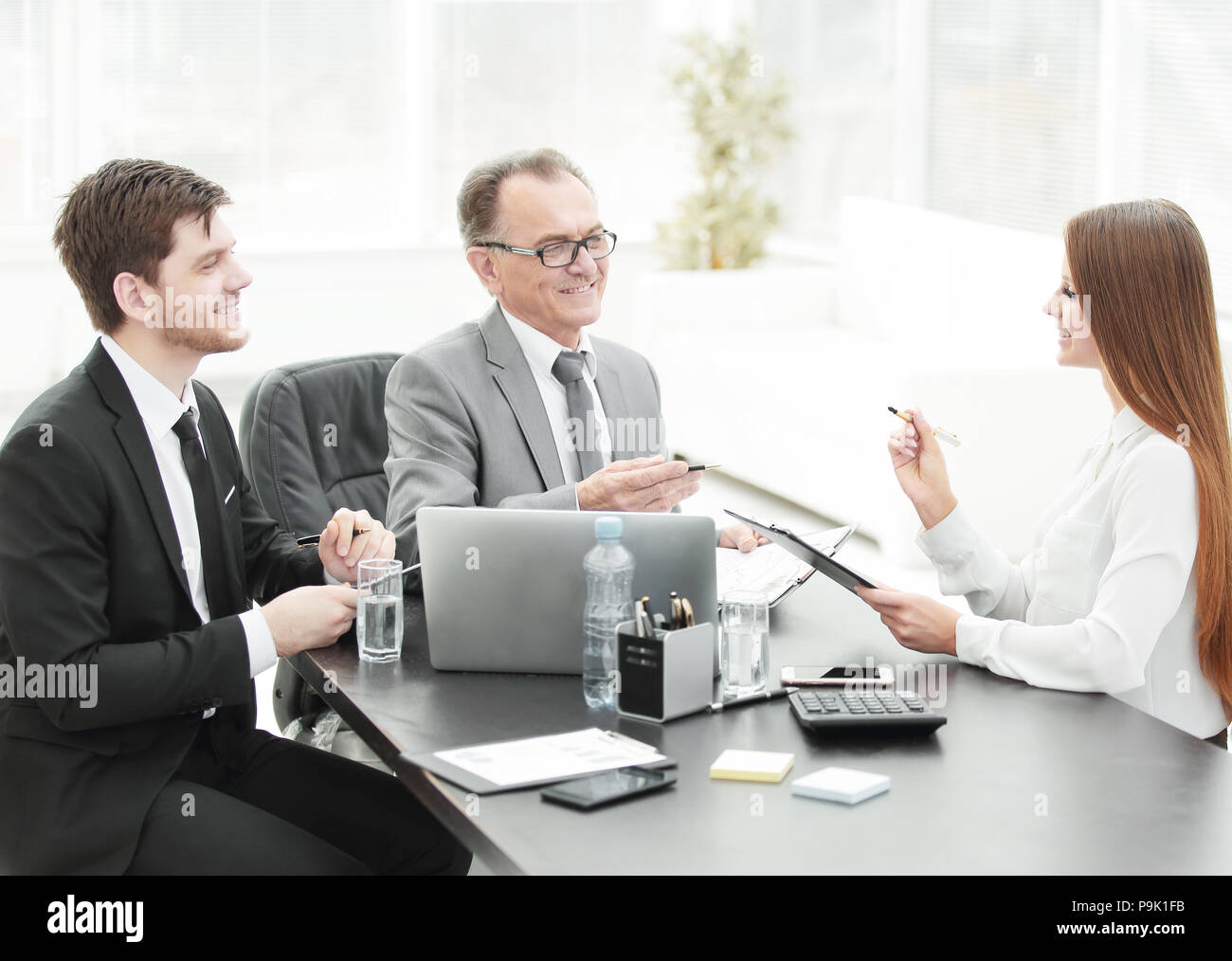 Manager discussing work issues with his assistants behind a Desk - Stock Image