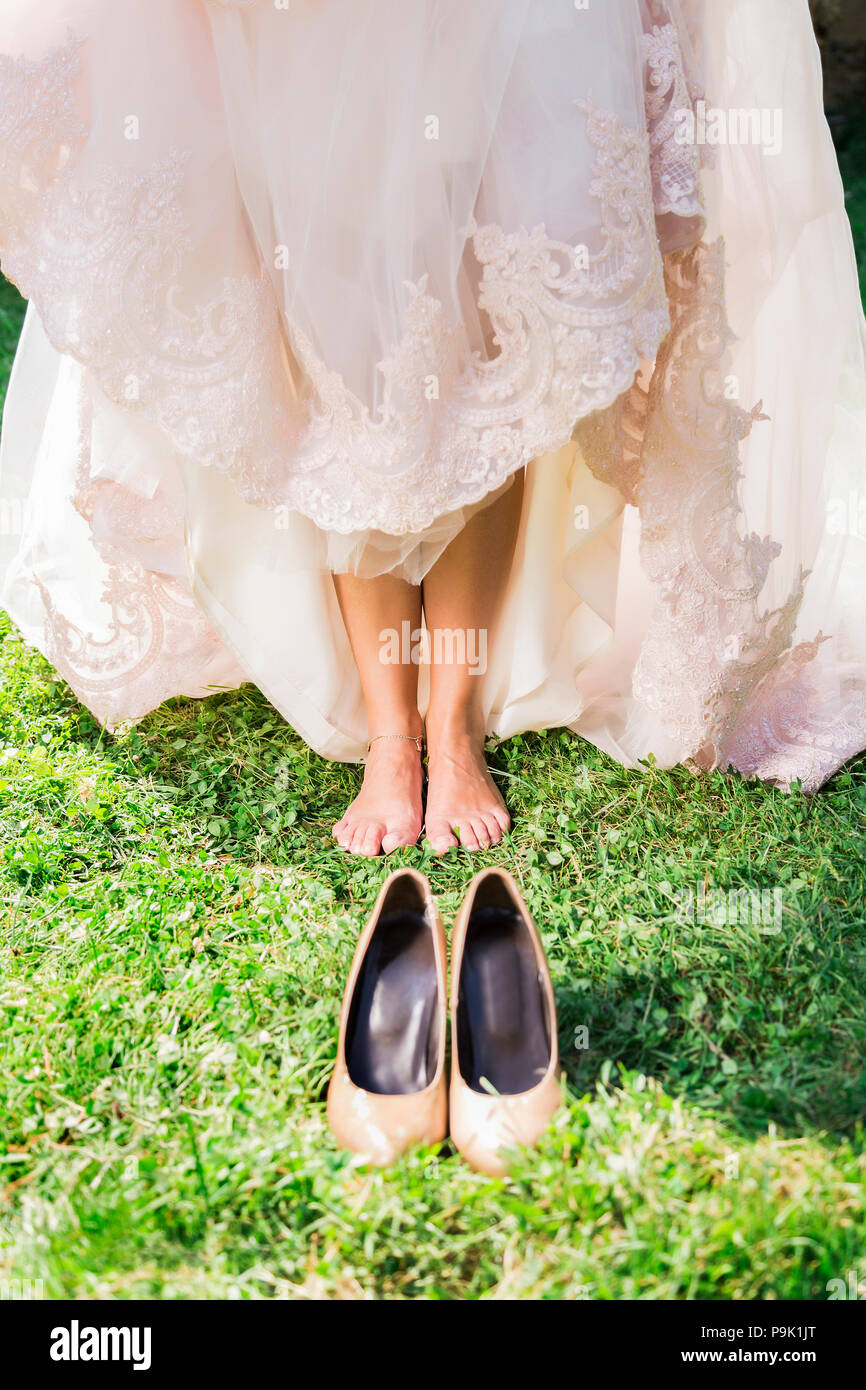 Barefoot bride on grass with shoes Stock Photo