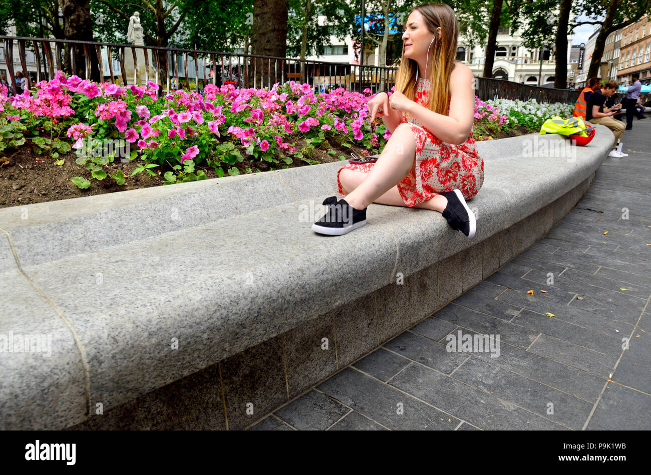 Young woman sitting listening to music on headphones in Leicester Square, London, England, UK. - Stock Image