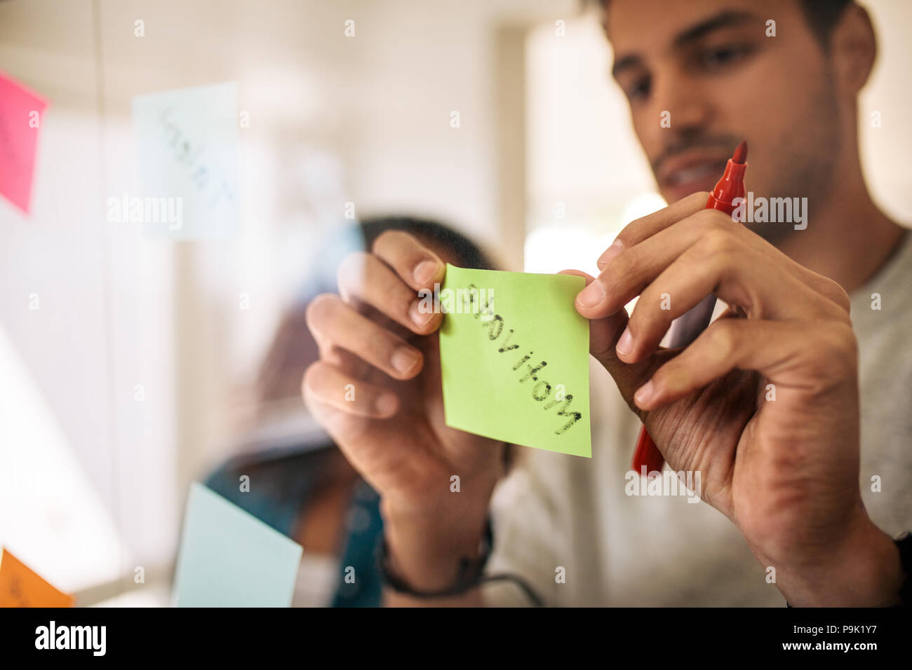 Man writing on sticky notes with marker pen and pasting on glass board in office. Entrepreneurs discussing business ideas and plans with sticky notes  Stock Photo
