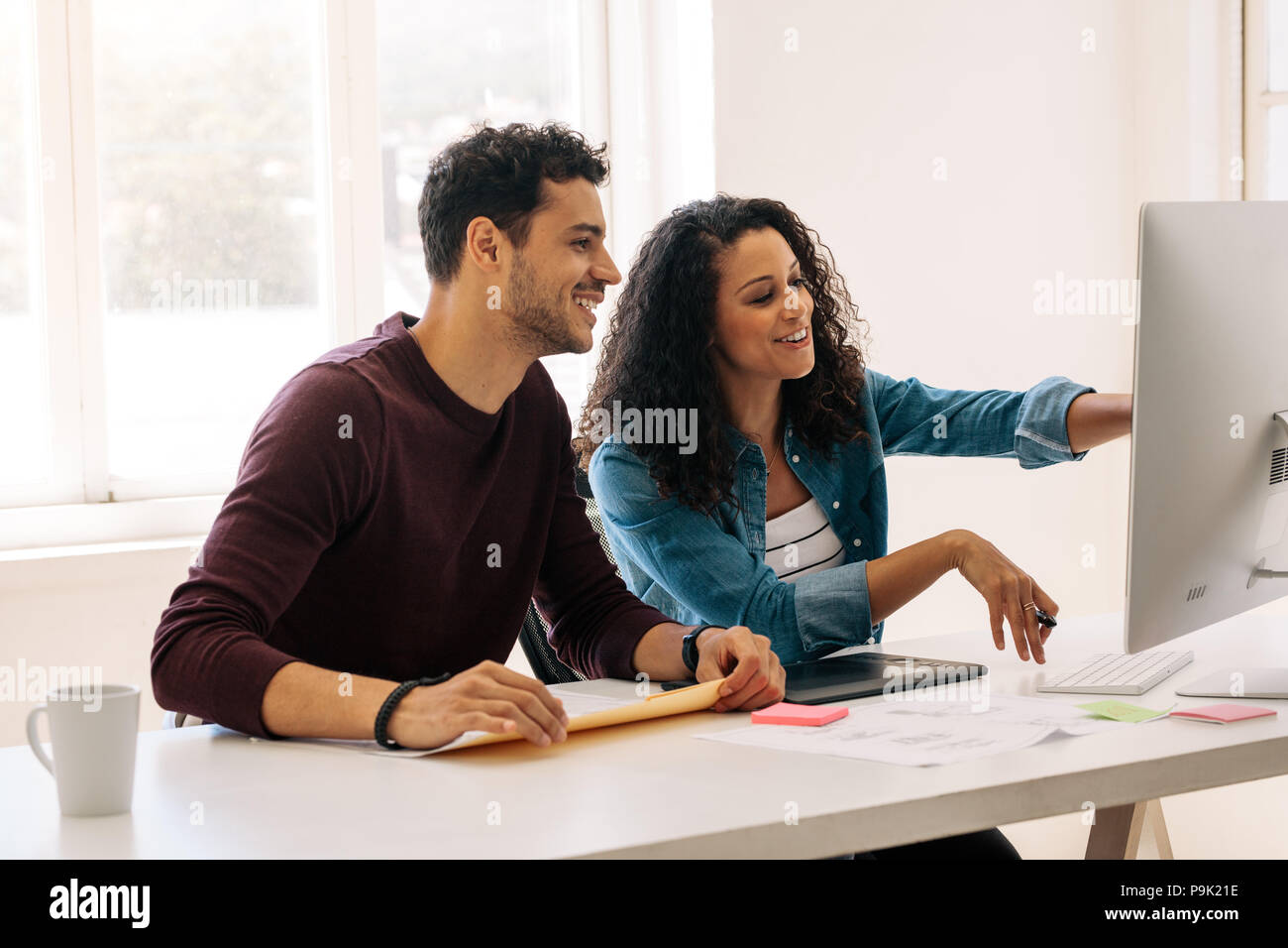 Businesswoman pointing towards the computer with a digital writing pad on the table. Woman entrepreneur discussing work with colleague sitting at her  - Stock Image