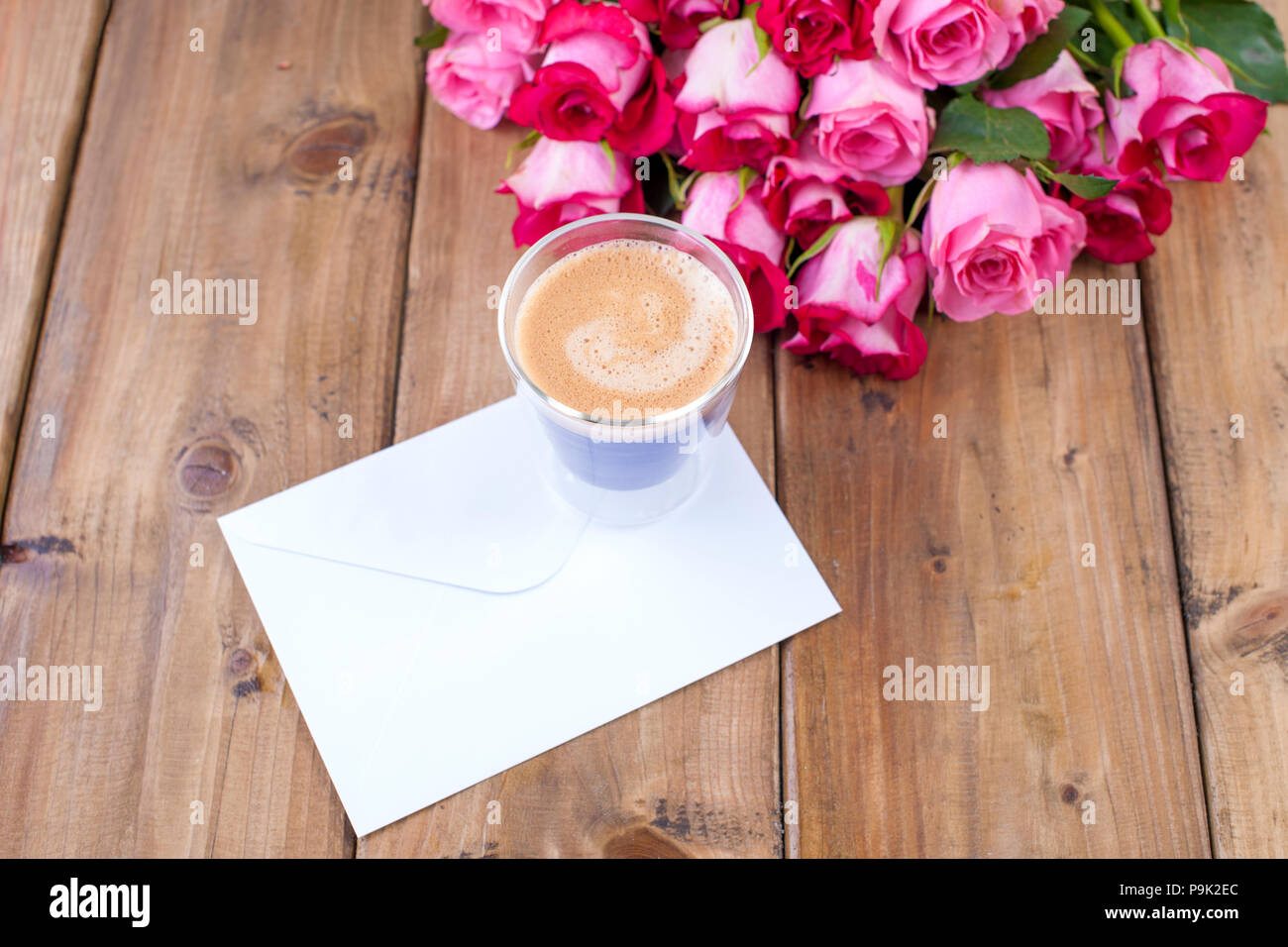 A bouquet of fresh pink roses and a glass of espresso. Wooden background. Free space for text or postcards. White envelope for writing. - Stock Image