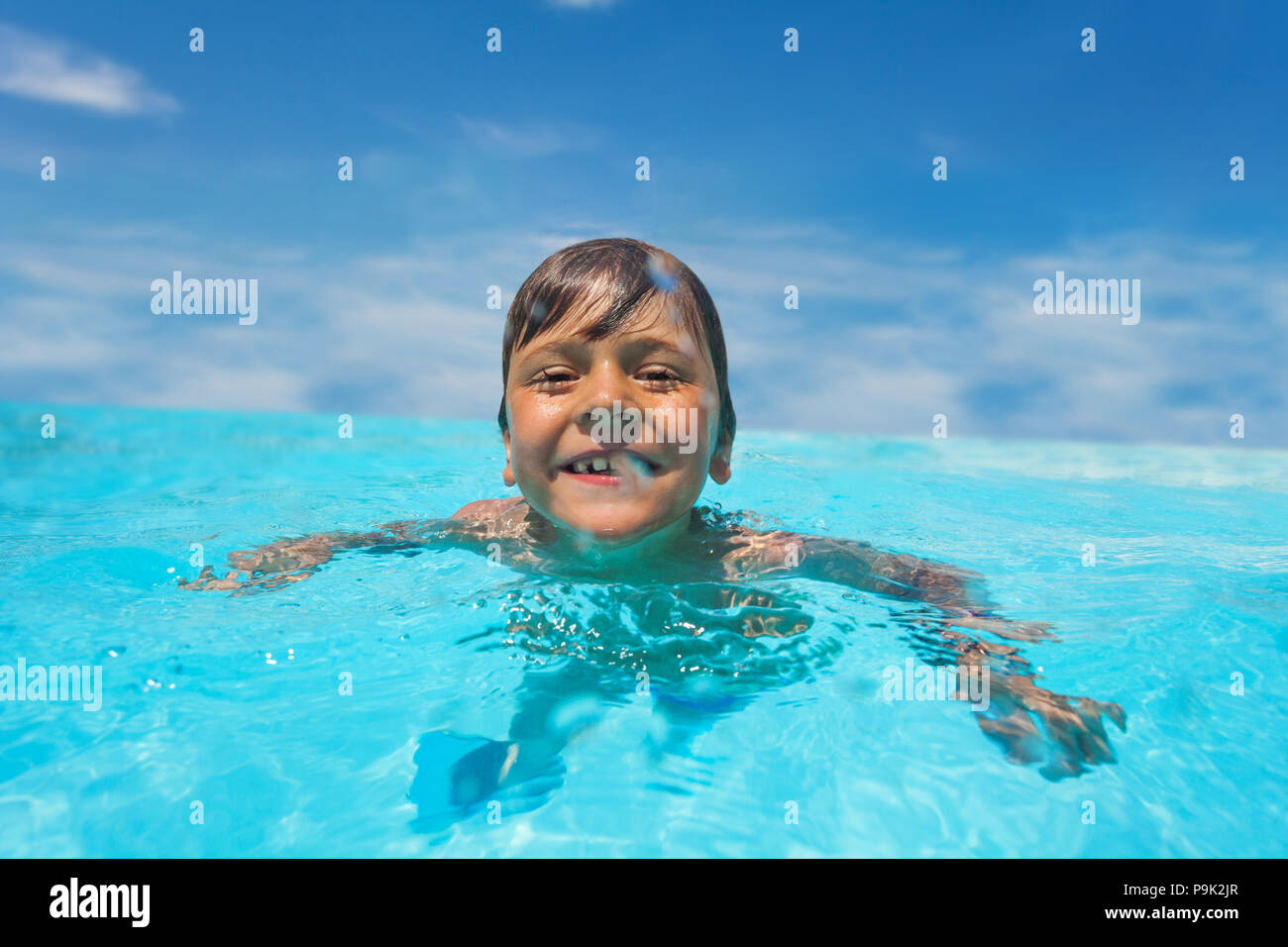 Portrait of laughing preteen boy swimming in crystal-clear water of outdoor pool - Stock Image