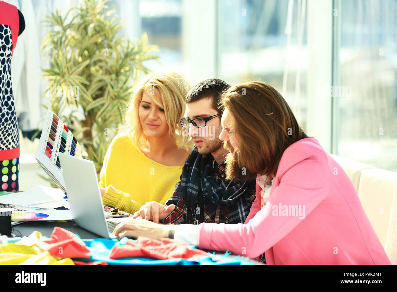 designer group works on a laptop in a creative office - Stock Image