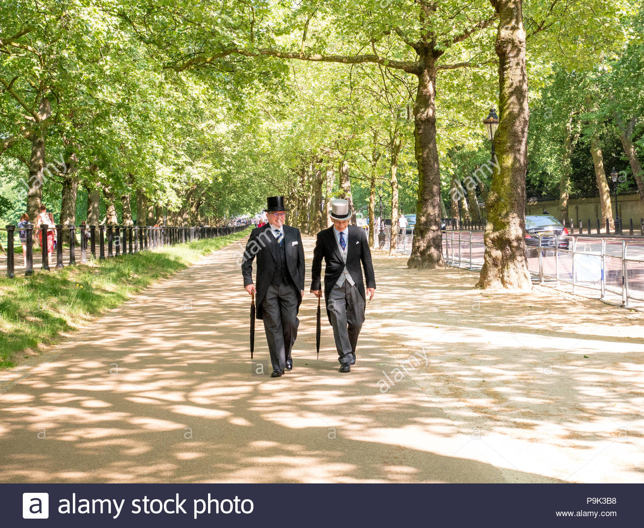 Men in morning suit and top hats strolling down Constitution Hill alongside Green Park, London, UK - Stock Image