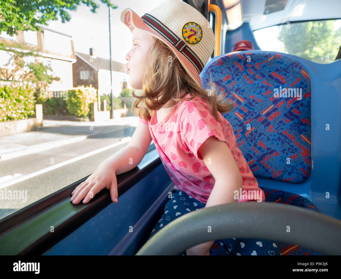 Young three year old girl looking out of a bus window, London, UK - Stock Image