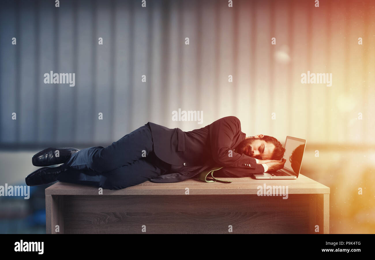 Businessman sleeping over a desk due to overwork - Stock Image