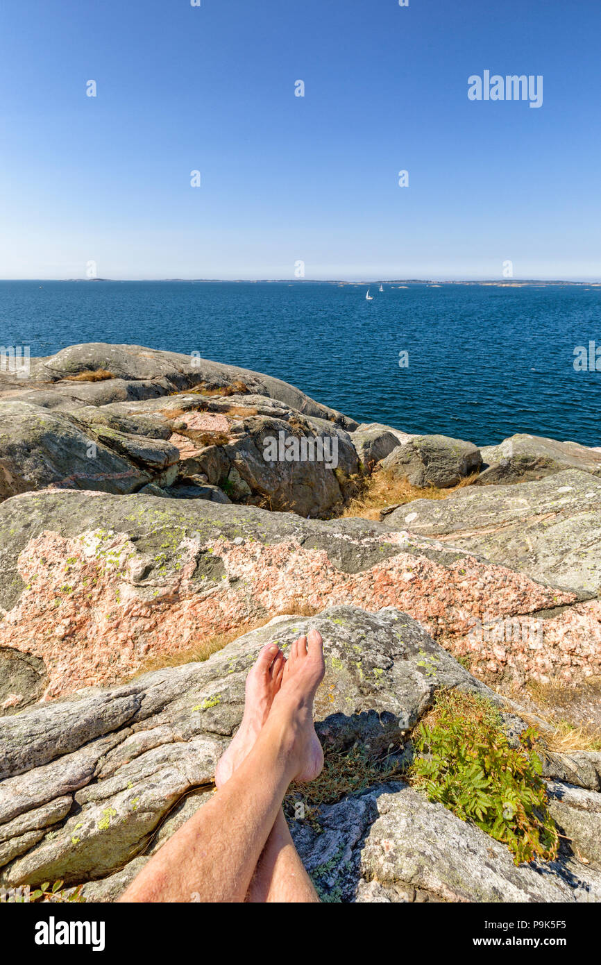 Close up view of man's bare feet relaxing on typical Swedish west coast granite rocks in front of a beautiful ocean summer landscape seascape view - Stock Image