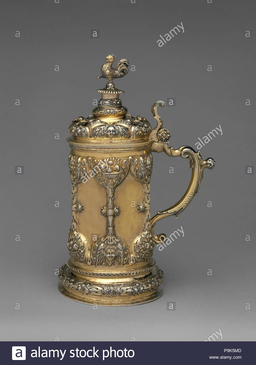 Tankard, late 17th century, Hungarian, Brassó, Gilded silver, Overall: 11 3/4 x 5 1/4 in. (29.8 x 13.3 cm), Metalwork-Silver, It is unclear if this tankard was made for private use or if it was always intended to serve as a communion vessel, which was its function after it arrived in England. The overall ornamental symbolism is connected to vanity. - Stock Image