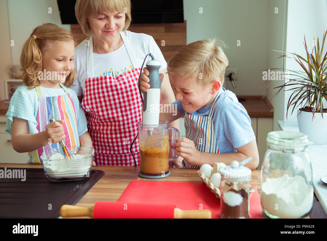 Happy grandmother with her grandchildren having fun during baking muffins and cookies - Stock Image
