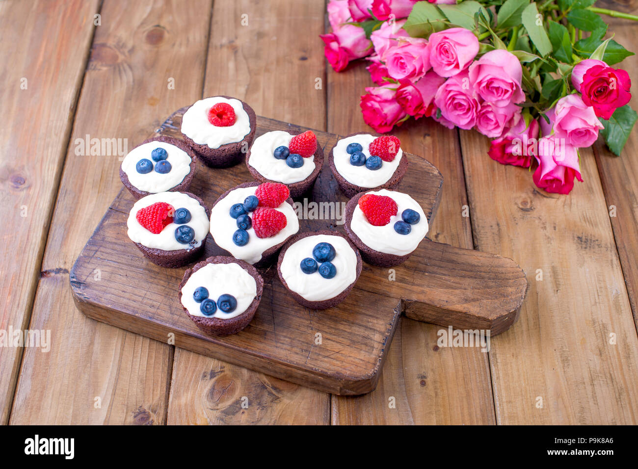 Flower bouquet cake mothers day stock photos flower bouquet cake chocolate muffins with raspberries and blueberries and white cheese cream on a brown wooden izmirmasajfo