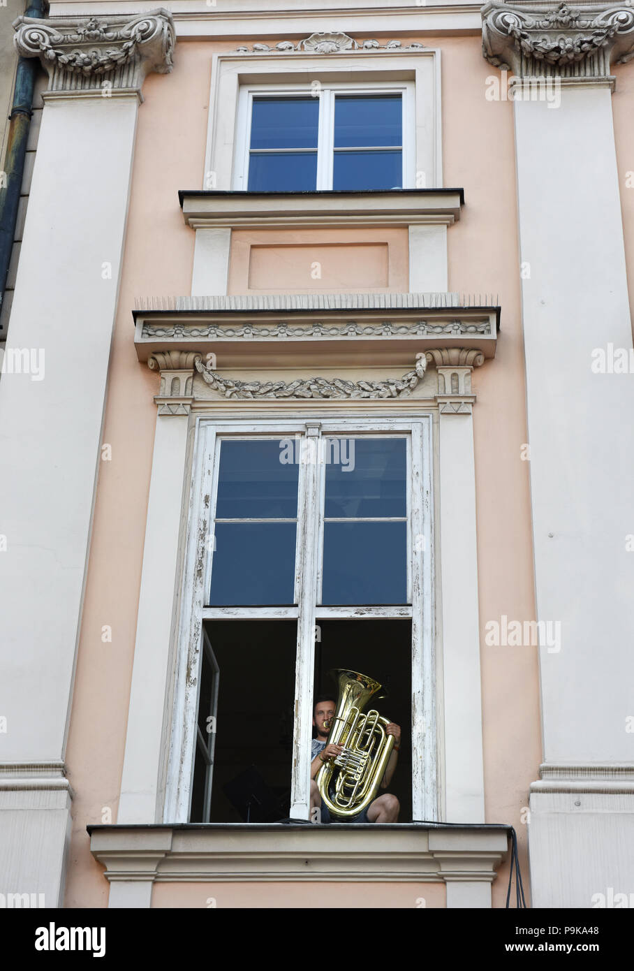 Musician playing performing from apartment windows in Krakow Poland - Stock Image
