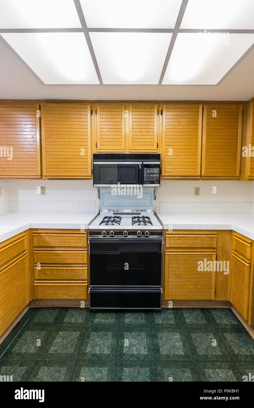 Charmant Old Condo Kitchen Vertical View With Oak Cabinetes, Tile Countertops, Gas  Stove And Green Flooring. Unchanged Since 1988.