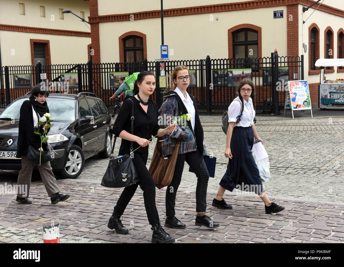 Last day at school! Girl pupils carrying a flower at the end of school term in Krakow Poland Stock Photo