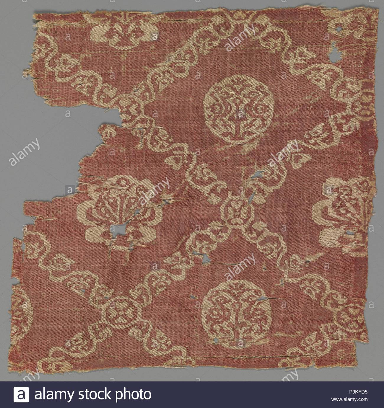 Vine Lattice with Birds, 6th–9th century, Attributed to Egypt, possibly Akhmim (former Panopolis), Silk; samit, Textile: L. 6 1/8 in. (15.5 cm), Textiles-Woven, This two-toned silk fragment features circular and lobed medallions composed of pairs of birds. These medallions are framed within an overall lattice pattern composed of abstracted vines, scrolls, and leaves. - Stock Image