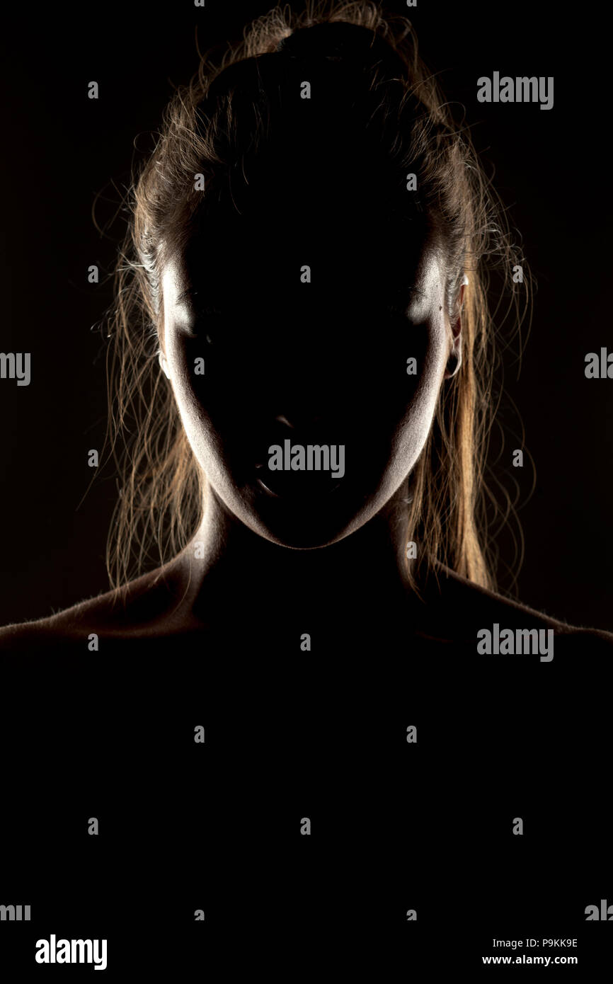 Mysterious portrait of woman in shadow on dark background - Stock Image