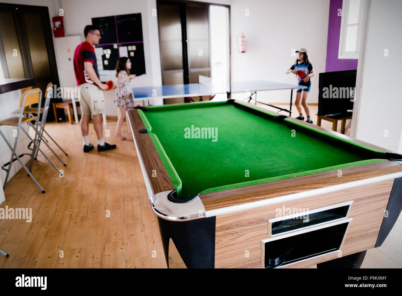 A games room with pool table in front of a family - the father is playing table tennis with his daughters in the bright bar and leisure centre - Stock Image