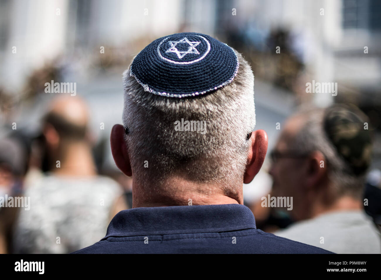 Bonn, Germany. 19th July, 2018. A resident from Bonn demonstrating at the market square with a Kippah on his head. Hundreds of people have demonstrated against anti-semitism. Many of them wore a kippah. Bonn reacted to an attack on an Israeli professor with the 'Kippah day'. The alarmed police mistakenly thought the academic was the offender and overpowered him. Credit: Federico Gambarini/dpa/Alamy Live News - Stock Image
