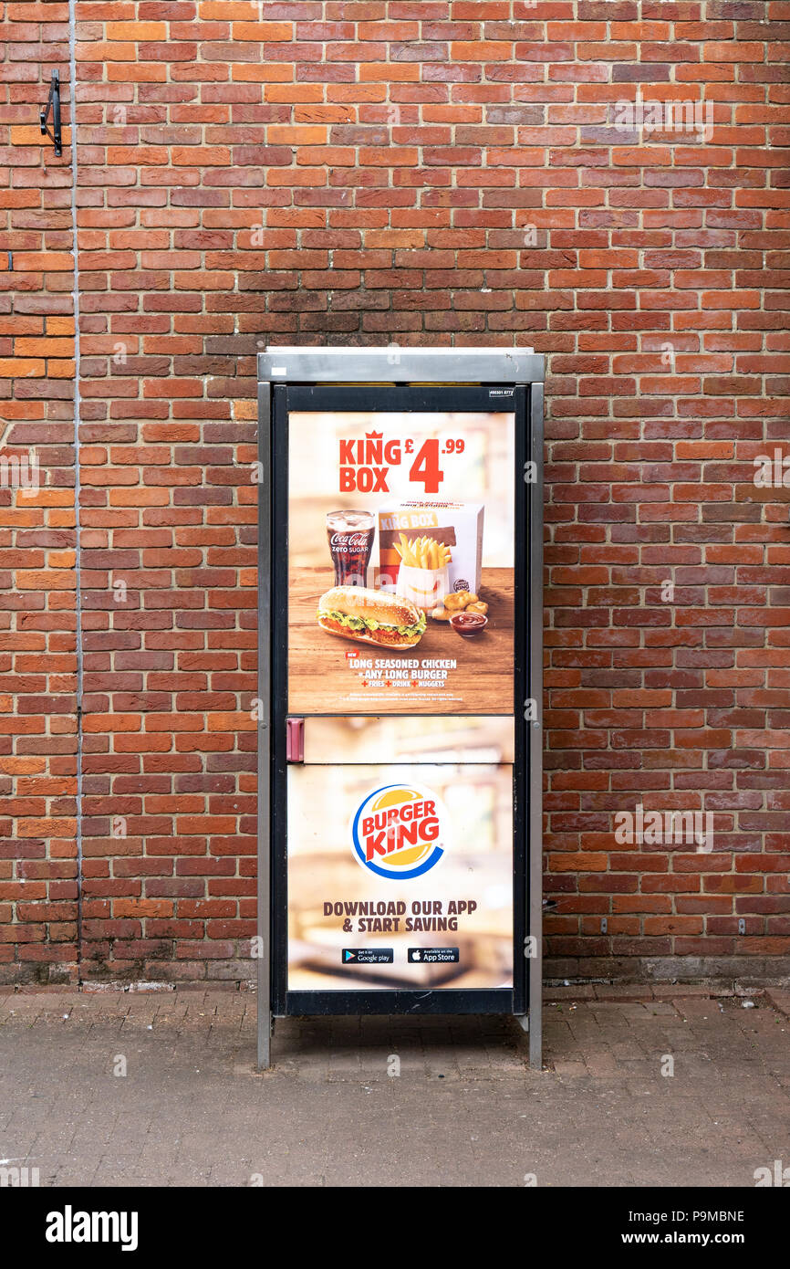 Burger King advertising posters on a UK telephone box - Stock Image