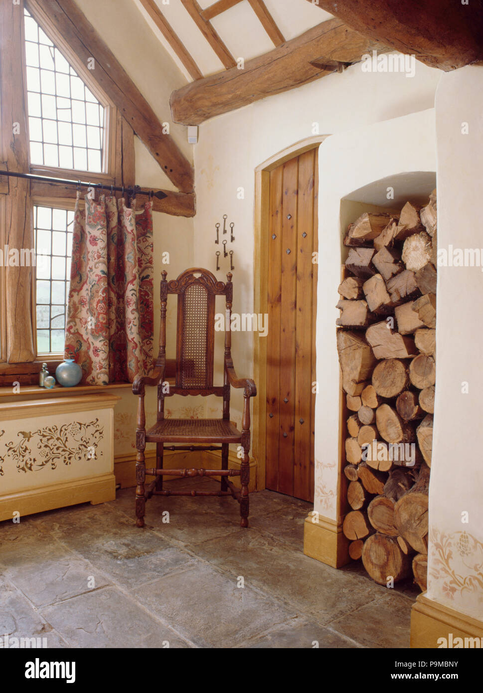Jacobean chair in corner of country hall with stone floor and logs stored in tall alcove Stock Photo