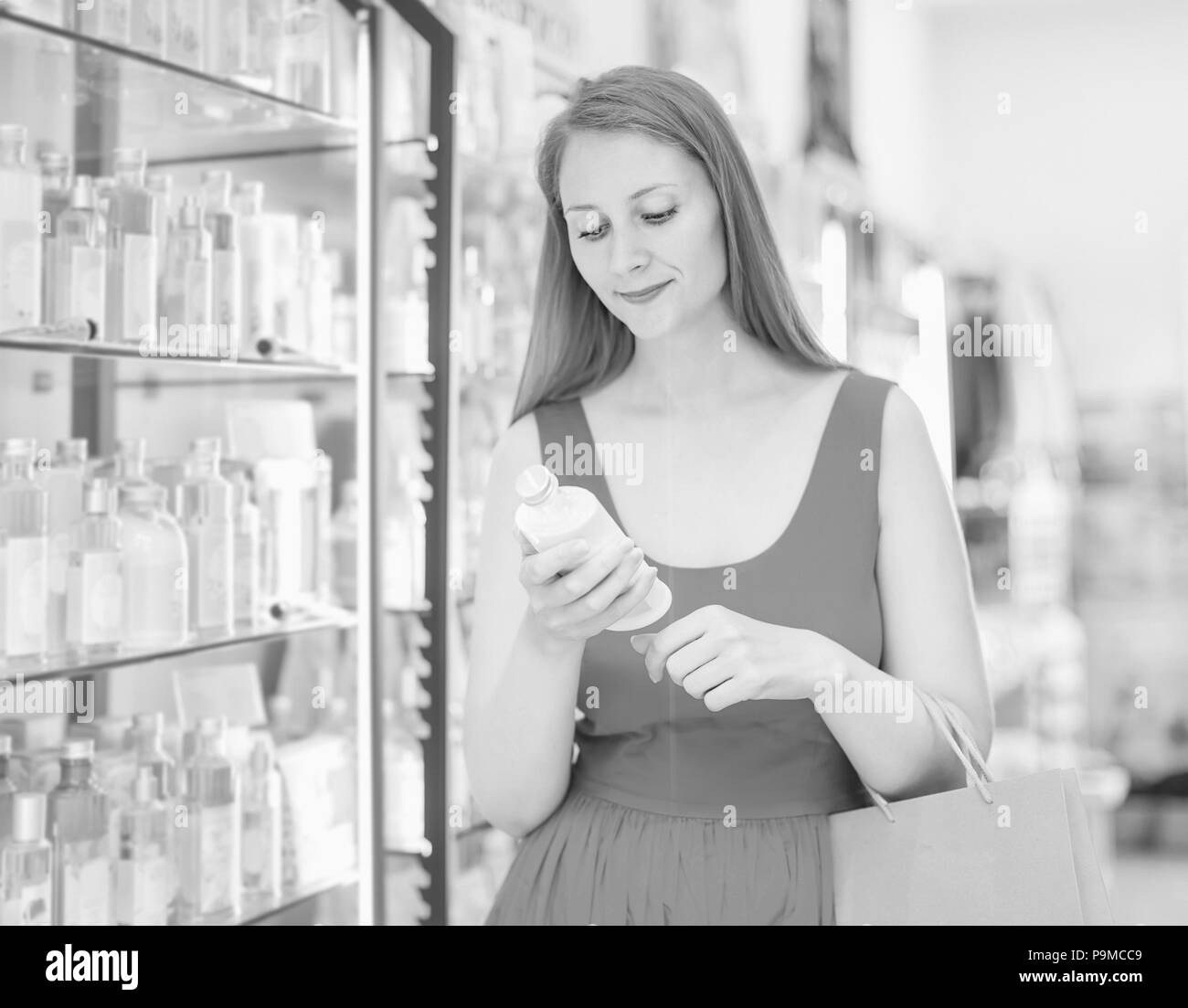 positive female choosing perfume conditioner in shopping mall - Stock Image