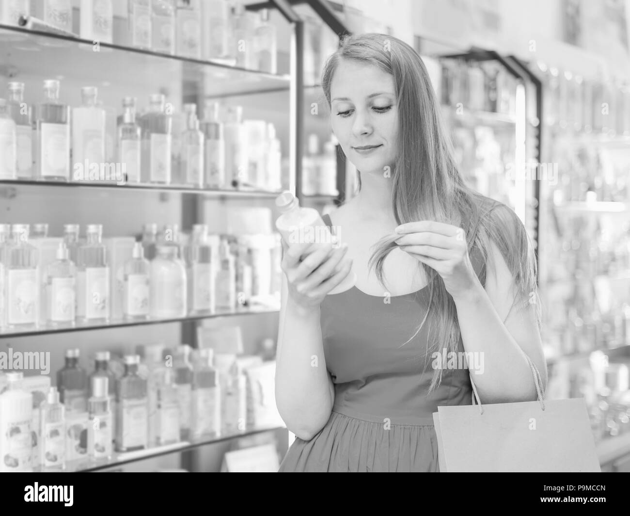 happy female choosing perfume conditioner in shopping mall - Stock Image