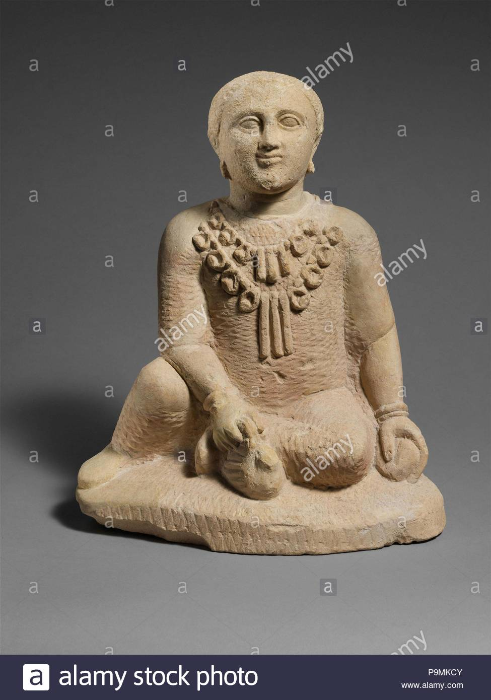 Limestone temple boy, Classical, late 5th century B.C., Cypriot, Limestone, Overall: 15 1/4 x 12 x 8 in. (38.7 x 30.5 x 20.3 cm), Stone Sculpture, He sits on a roughly elliptical plinth. His left hand holds a fruit or ball. His right arm stretches down to hold a bird by its wings near his left foot. He wears two strings of seals with oblong pendants in the middle. - Stock Image