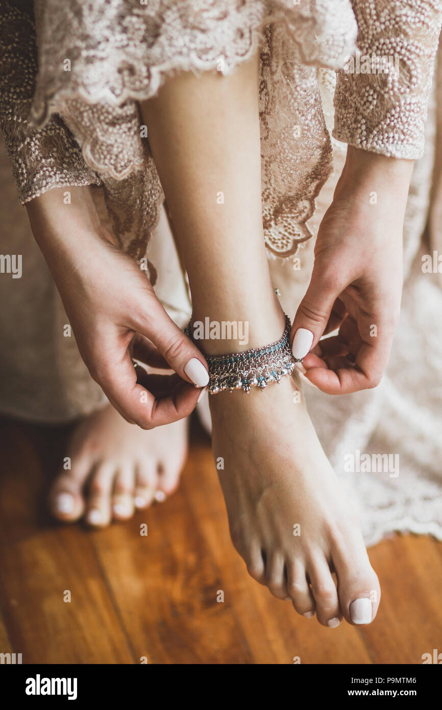 Bride wearing silver metal adornment bracelet on feet, beautiful beige lace dress - Stock Image