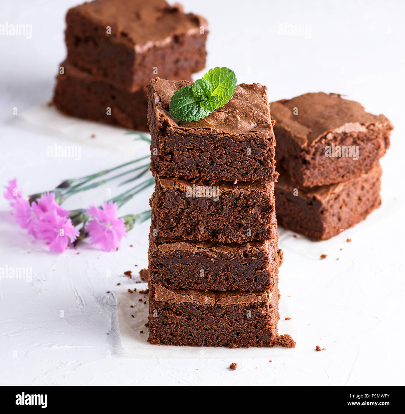 stack of square pieces of baked brown brownie pie, close up - Stock Image