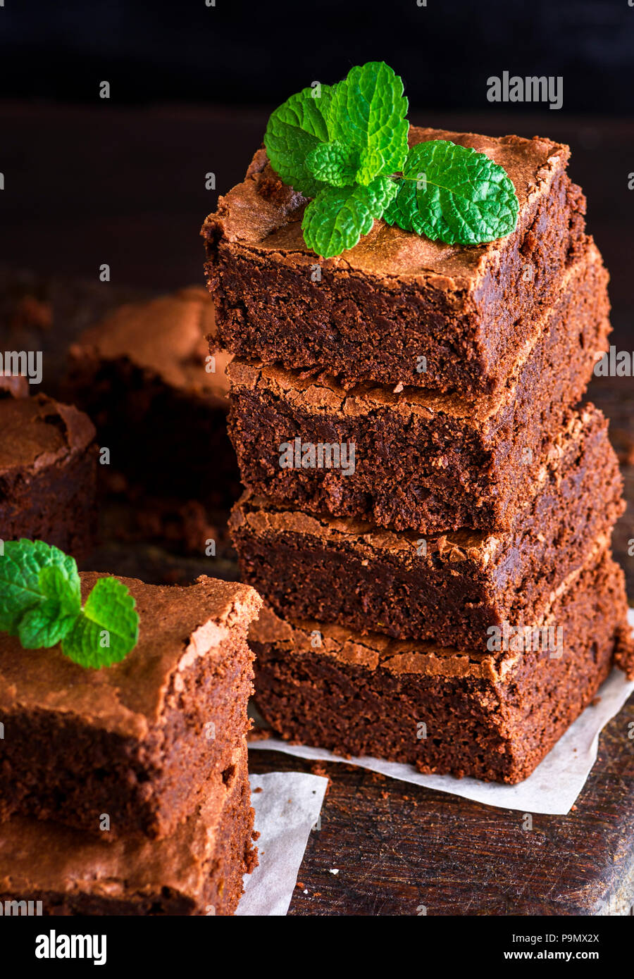 Baked square pieces of chocolate brownie pie are stacked, on top of a green sprig of mint - Stock Image