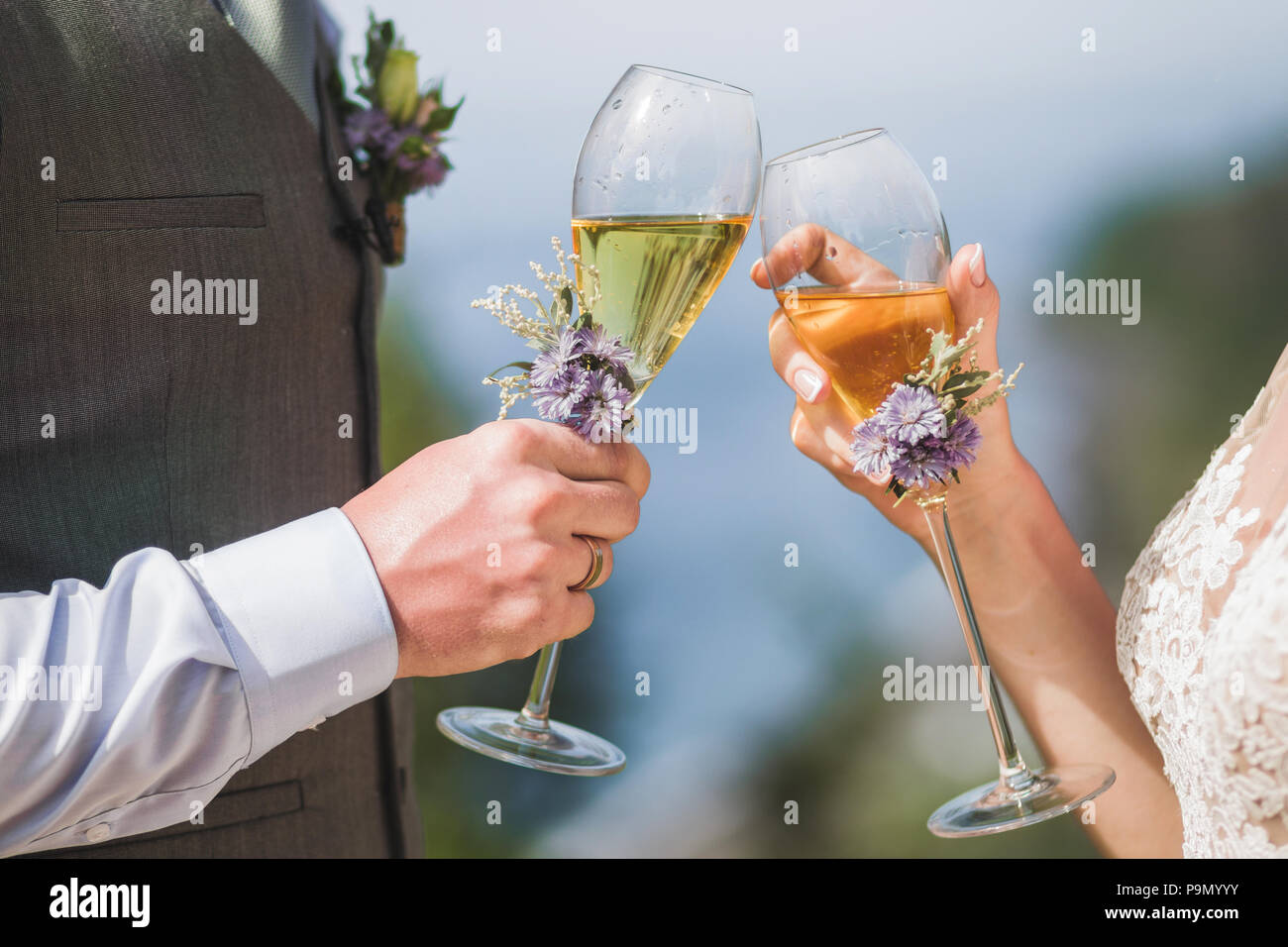 Man and woman hands holding two champagne glasses decorated with flowers for wedding ceremony - Stock Image