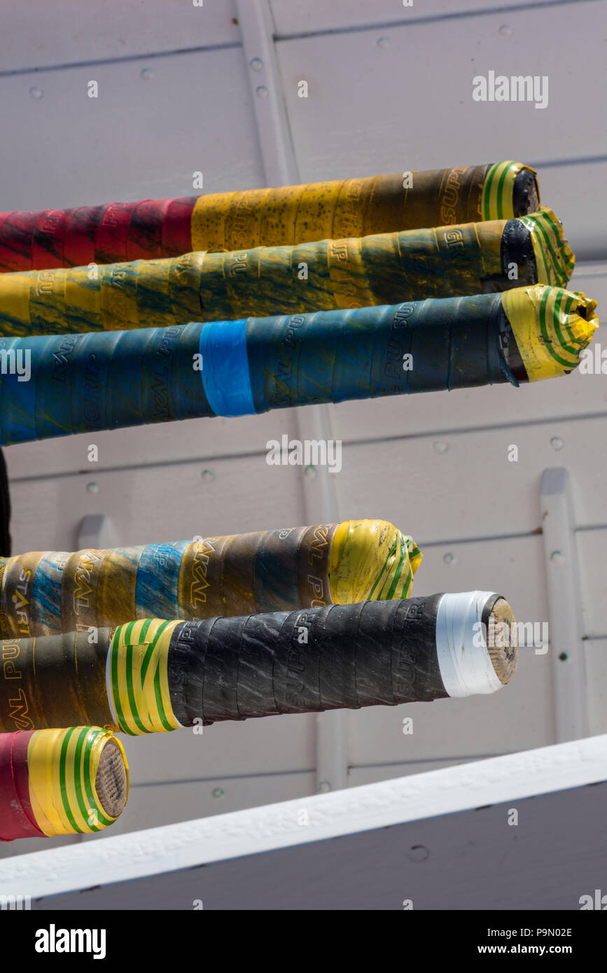 colourful handles on skulling oars in a boat used for rowing races. traditional wooden rowing equipment. - Stock Image