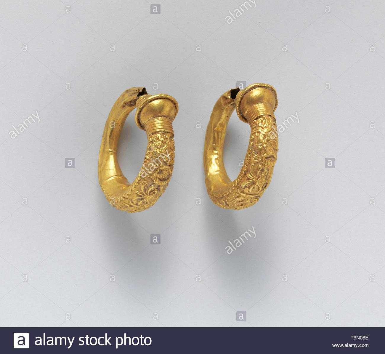 Gold trumpet-shaped earrings with relief decoration, Classical, 5th–4th century B.C., Etruscan, gold, Diam.: 1 1/2 in. (3.8 cm)(both), Gold and Silver, Decorated in floral repoussé patterns of palmettes and acanthus leaves. - Stock Image