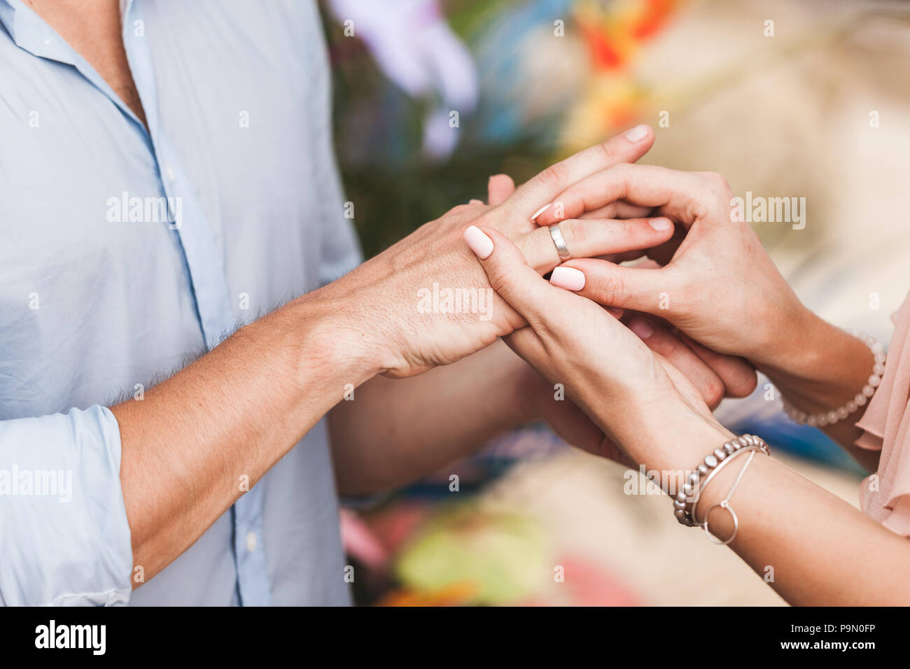 Woman wearing ring on man's hand on wedding ceremony close-up - Stock Image