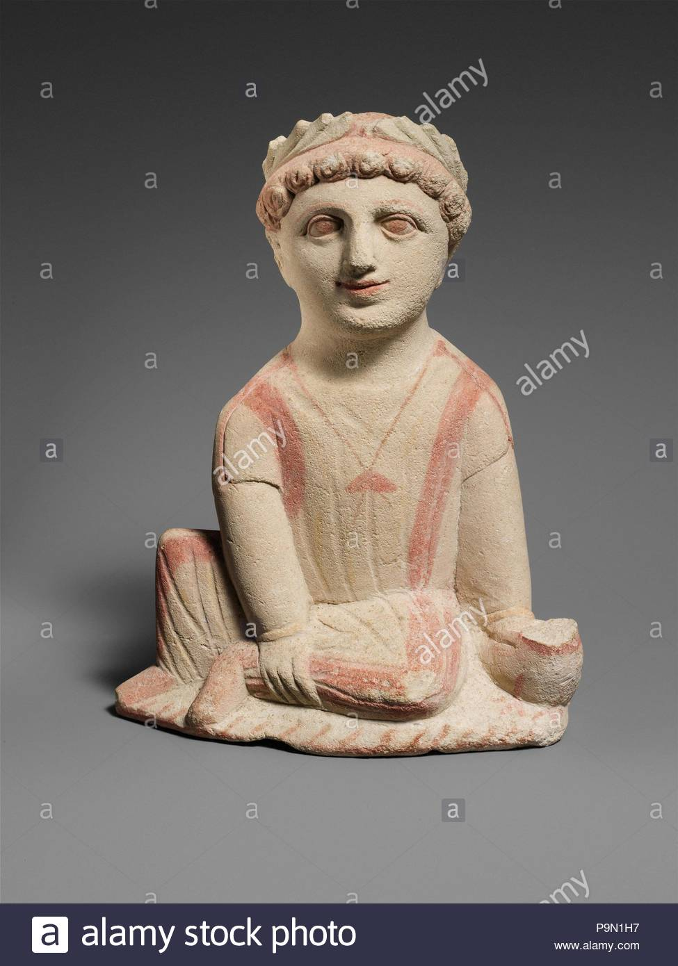 Limestone statuette of a temple boy, Classical, ca. 350–300 B.C., Cypriot, Limestone, Overall: 9 1/4 x 7 x 2 1/2 in. (23.5 x 17.8 x 6.4 cm), Stone Sculpture, He sits on an elliptical plinth. His left foot is also stretched downwards and holds a bird, whose head is missing. He wears a short sleeved chiton that reaches his ankles. Thick bands are painted on his sides and legs. - Stock Image
