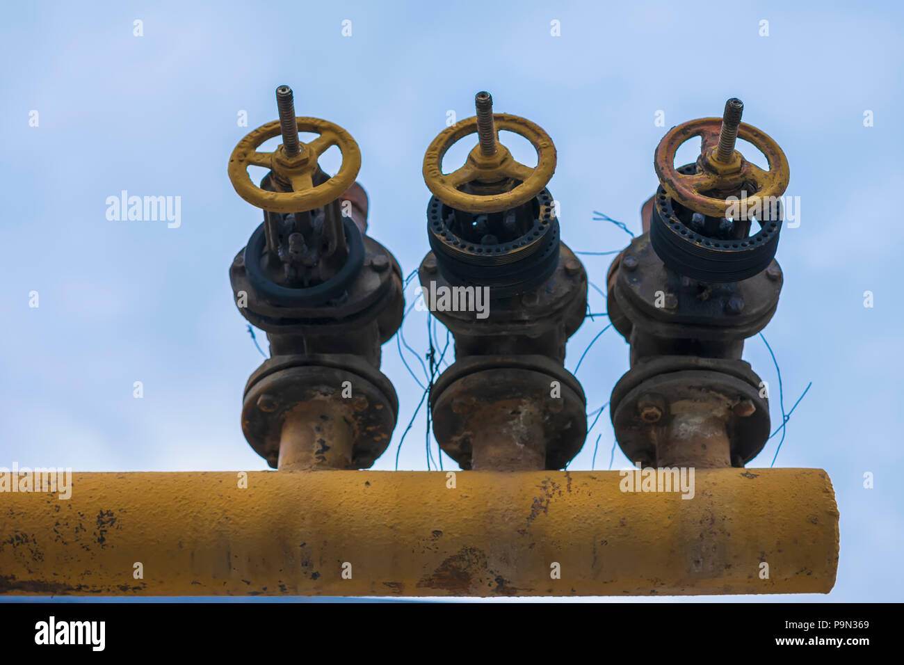 Three old iron pipe with valve, crane mechanism on sky background close-up Stock Photo