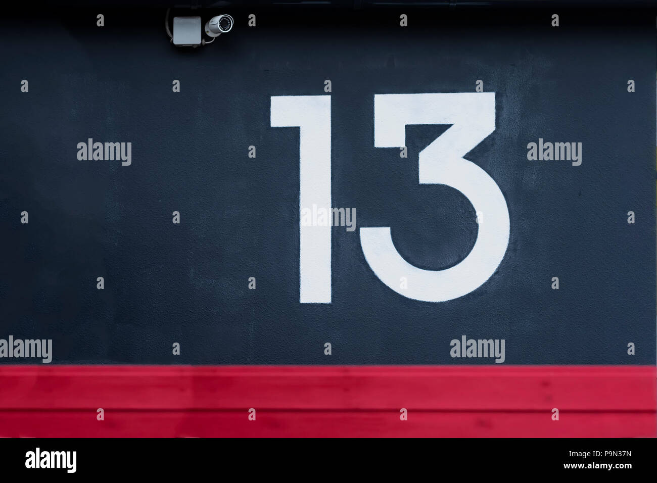 Written number thirteen on the blue concrete wall with camera surveillance - Stock Image