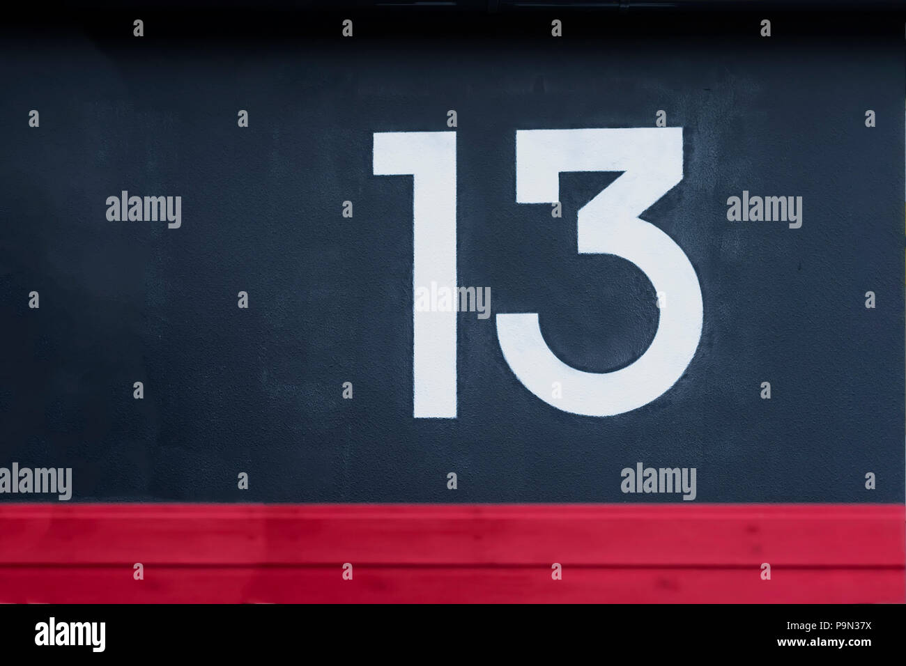 Written number thirteen on the blue red concrete wall - Stock Image
