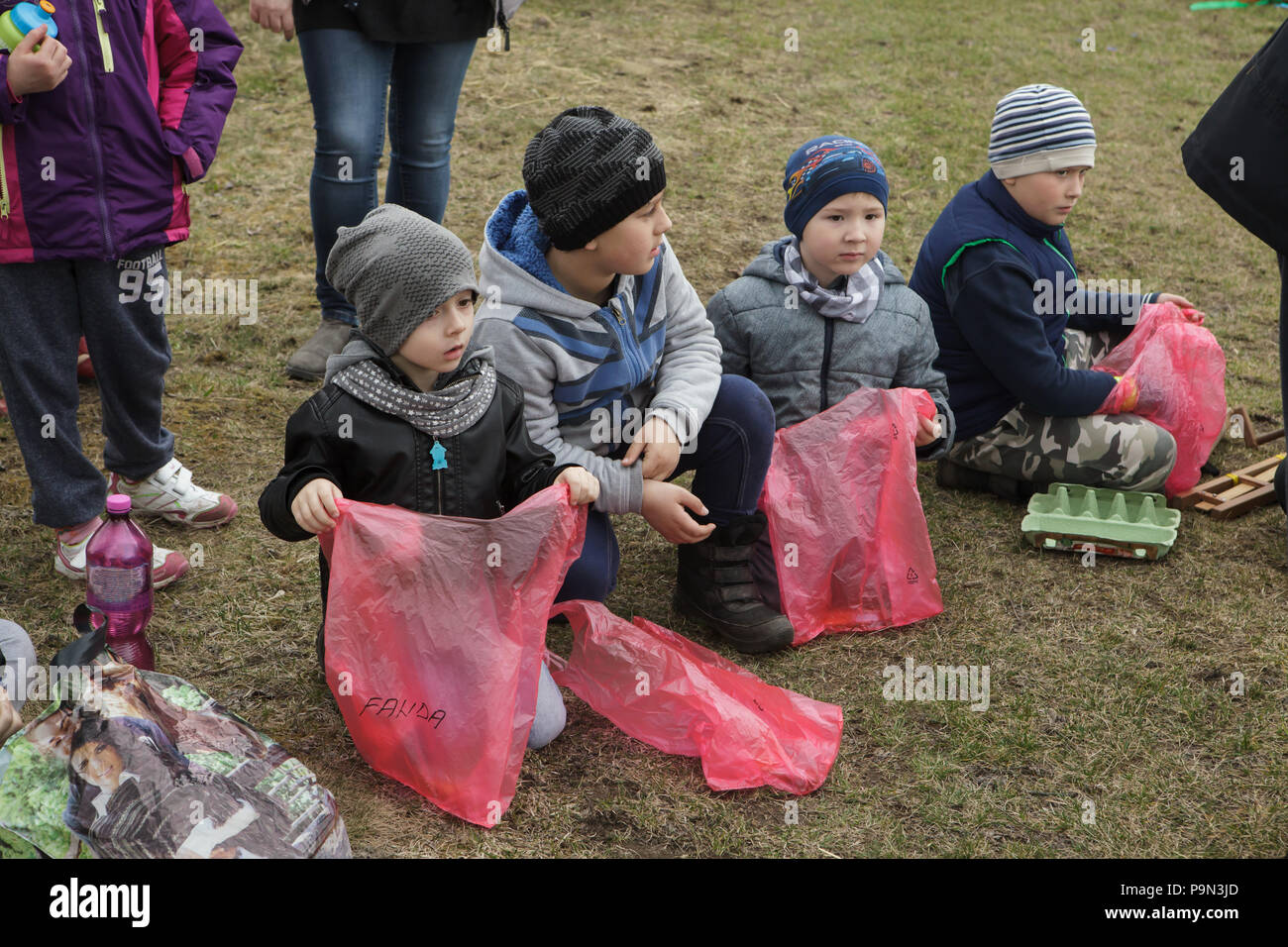 Traditional Easter procession known as Vodění Jidáše (Marching Judas) in the village of Stradouň in Pardubice Region, Czech Republic. Boys wait with empty plastic bags for their portions of sweets collected during the procession on 31 March 2018. Early in the morning on Holy Saturday, the eldest teenage boy in the village is dressed in a ridiculous straw suit. He is supposed to perform Judas Iscariot in this way. Wearing this obscure outfit, he has march through the village from house to house escorted by other boys, who twist wooden ratchets and sing a song about Judas, who betrayed his maste Stock Photo
