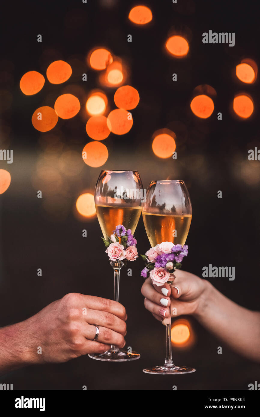 Two glasses of champagne in couple hands decorated with fresh flowers and light orange glare on background - Stock Image