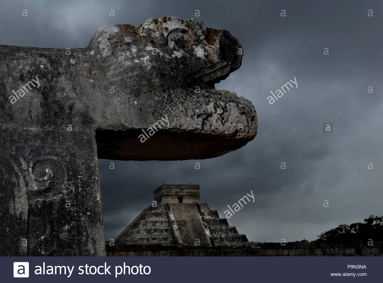 El Castillo and a stone carving of a mythological beast. - Stock Image