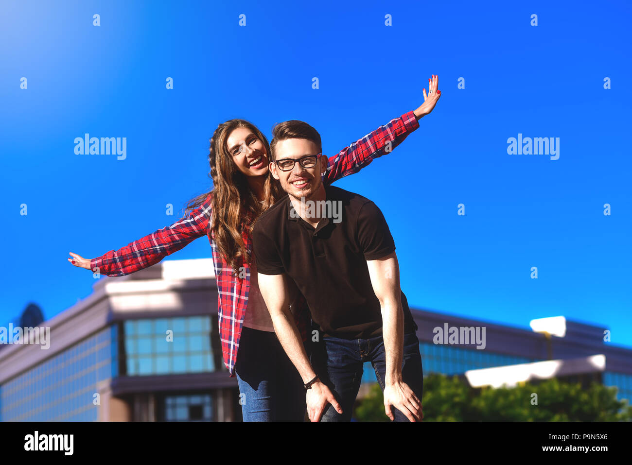 Outdoor shot of man giving woman piggyback. Man carrying woman oh his back - Stock Image
