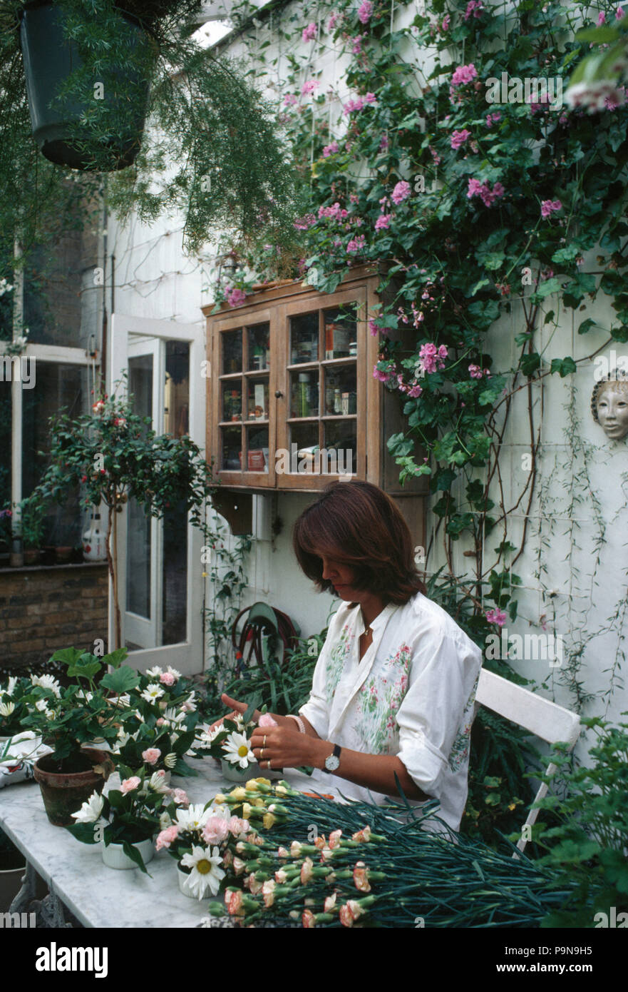 Woman arranging flowers in a conservatory         FOR EDITORIAL USE ONLY - Stock Image
