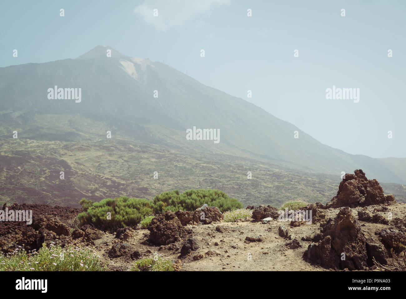 Mount Teide volcano in Tenerife hidden by the haze and sand of La Calima with arid scrubland and lava rock formations in the landscape - Stock Image