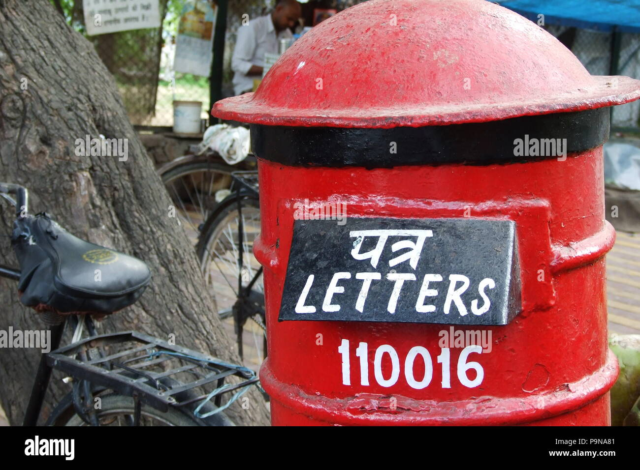 Red Postbox and bicycles India - Stock Image