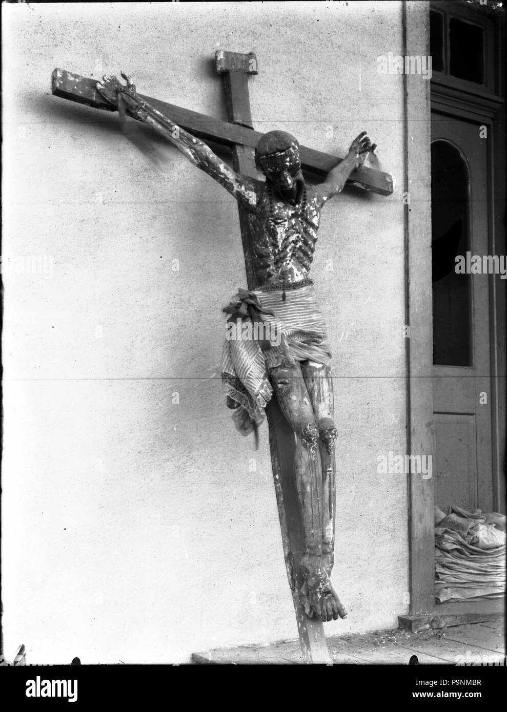 . English: A crucifix at Mission Santa Cruz, New Mexico, ca.1900 Photograph of a crucifix at Mission Santa Cruz, New Mexico, ca.1900. A large crucifix with Chist figure leans against and exterior wall. A cloth is tied around the loins of the figure. The cross stands on a wooden porch. A wood door is visible in the background near a pile of folded cloths.  Call number: CHS-4352 Legacy record ID: chs-m17091; USC-1-1-1-14102 Photographer: James, George Wharton Filename: CHS-4352 Coverage date: circa 1900 Part of collection: California Historical Society Collection, 1860-1960 Type: images; physica - Stock Image
