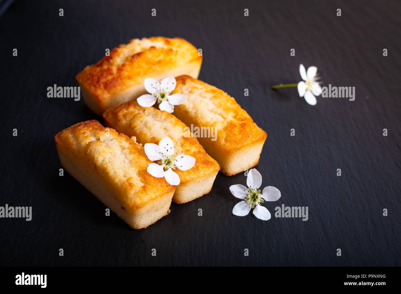 Food concept mini French almond cake financier on black slate stone with copy space - Stock Image
