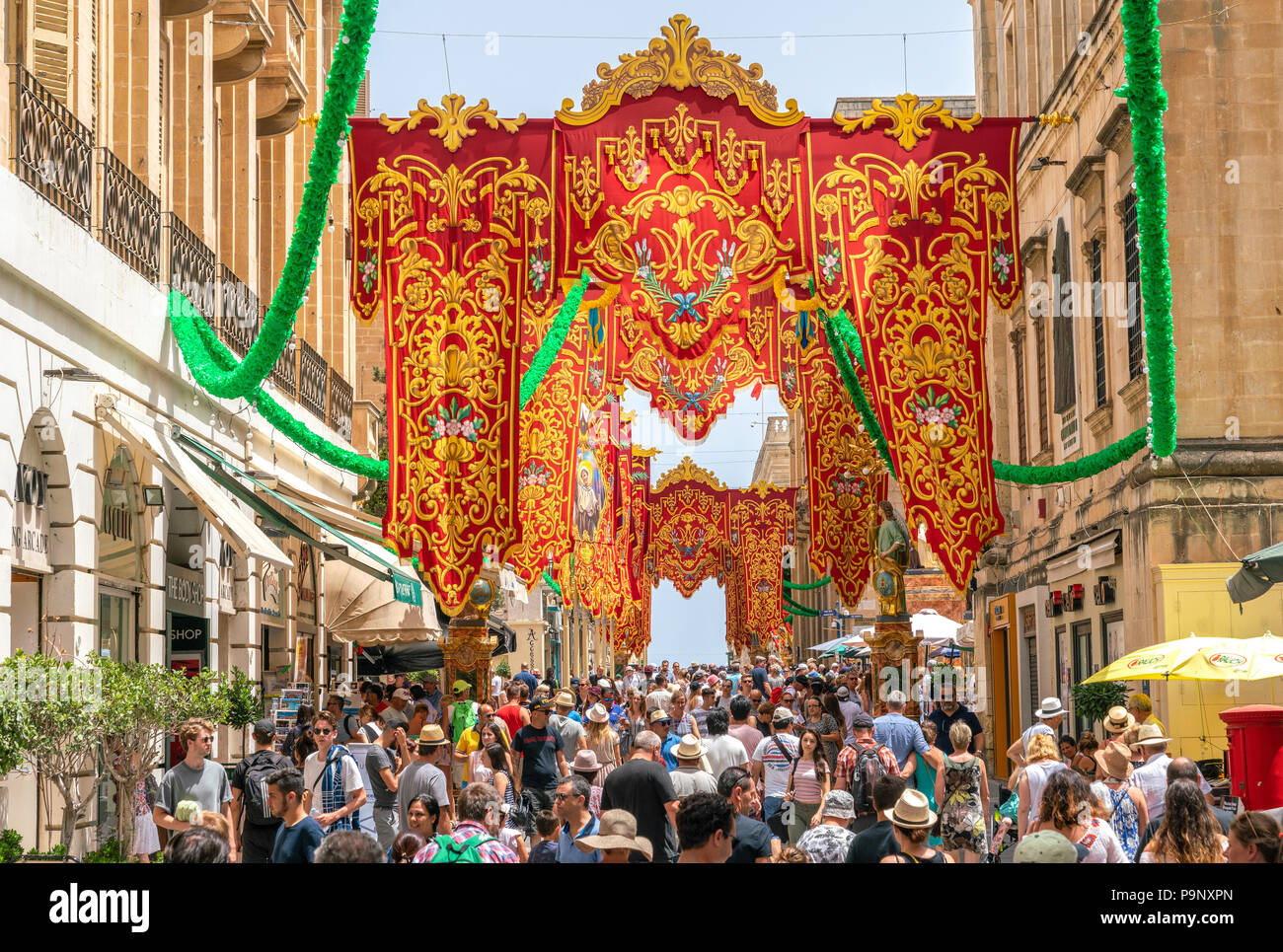 14 July 2018 - Valletta, Malta. Festively decorated the street with colourful banners for St Augustine Feast. People walking in the beautiful and busy old - Stock Image