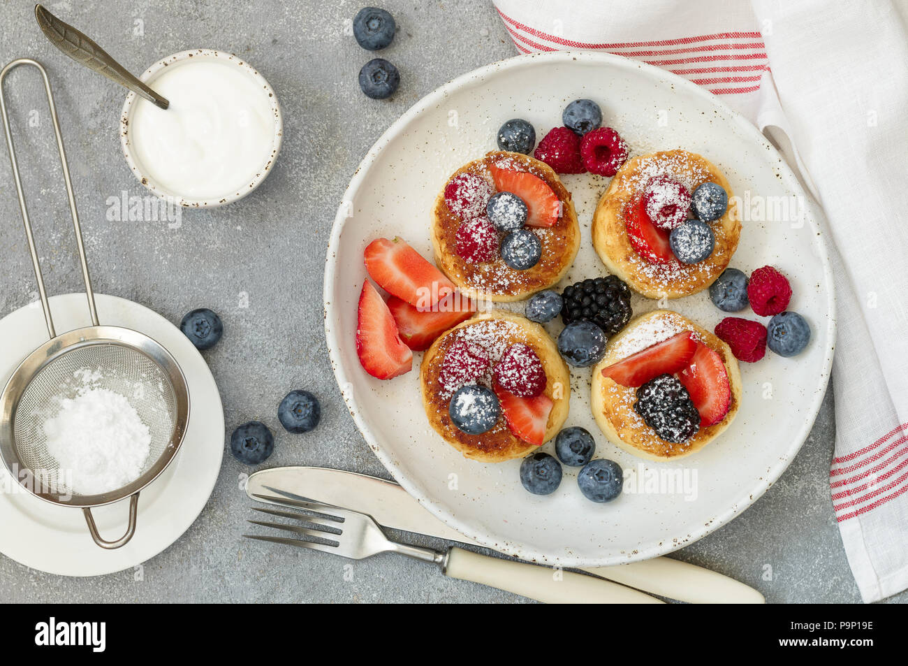 Cottage cheese pancakes, syrniki, curd fritters with fresh berries (raspberry, strawberry, blueberry, BlackBerry) and powdered sugar in a white plate. - Stock Image