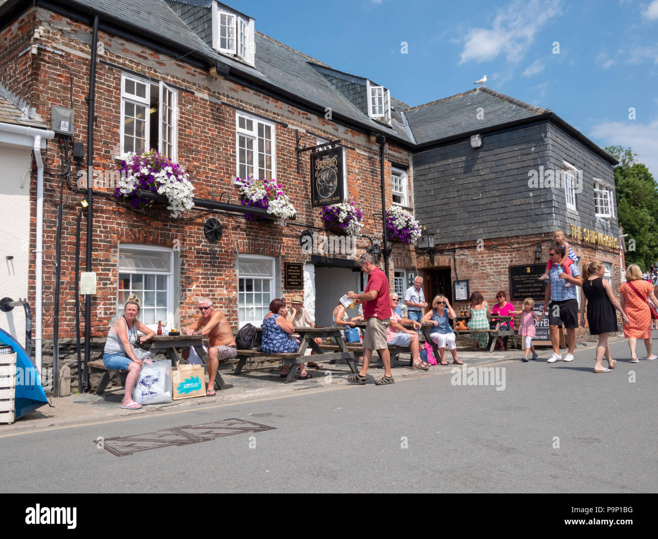 Tourists and customers sitting outside the Shipwrights Arms out on a hot summer day at Padstow Harbour Cornwall UK - Stock Image